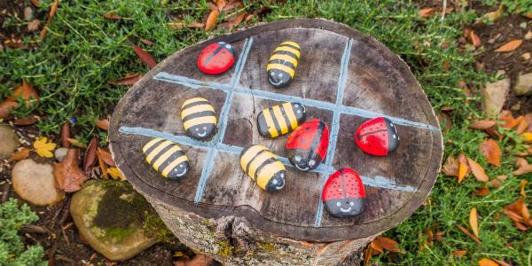 Tree trunk with bee and lady bugs in a tic tac toe pattern